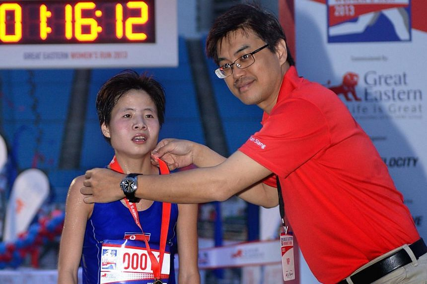 North Korean Kim Hye Gyong (left) being presented a medal by Great Eastern Singapore CEO Khoo Kay Siang after she crossed the finish line. -- ST PHOTO: LIM SIN THAI