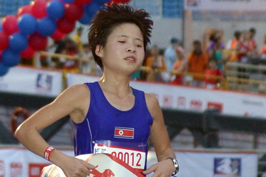 North Korean Kim Hye Song is the second runner to cross the finish line of the Great Eastern Women's half marathon event on Nov 10, 2013. -- ST PHOTO: LIM SIN THA