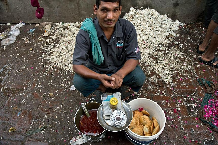 A street food vendor selling kachoris, a deep-fried snack, at a wholesale flower market in New Delhi. There are an estimated five million street food vendors in India, of whomabout 60,000 are in Delhi.