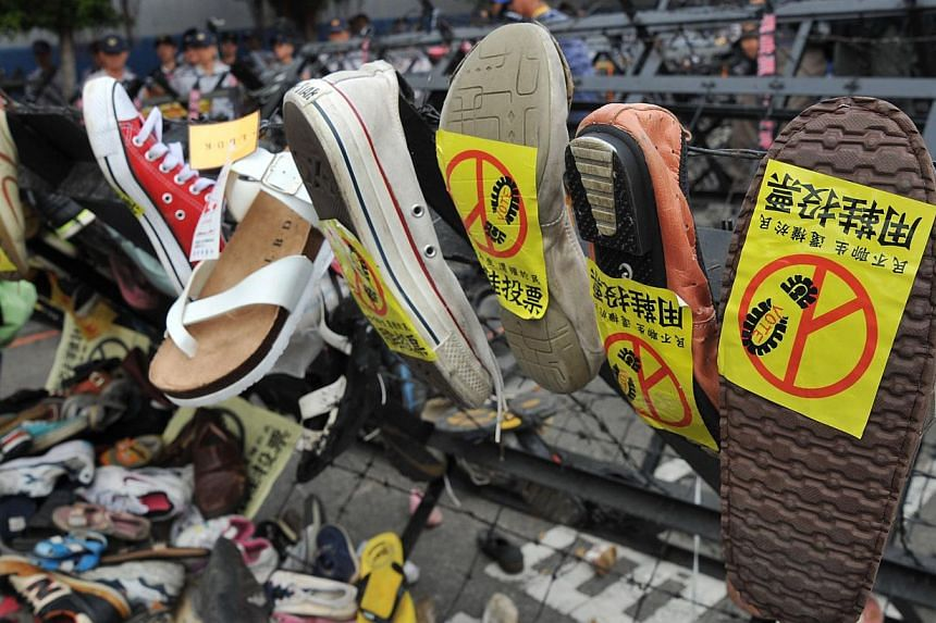 "Collected shoes of demonstrators are displayed with labels reading ""use the shoes to vote"" at a protest outside the national congress of the ruling Kuomintang (KMT) party in Taichung, on Nov 10, 2013. -- PHOTO: AFP"