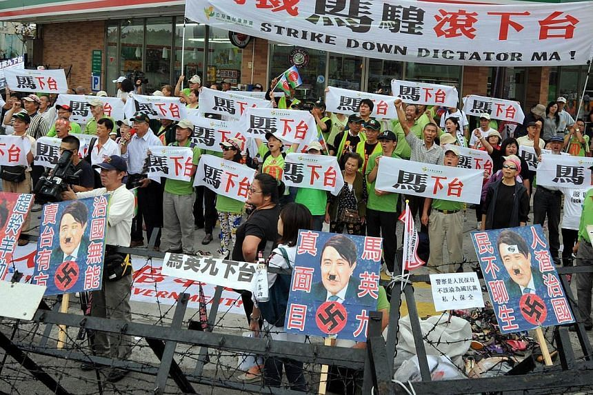 "Demonstrators chant slogans while hold banner read ""Ma Ying-jeou step down!"" during the protest outside the national congress of the ruling Kuomintang (KMT) party in Taichung on Nov 10, 2013. -- PHOTO: AFP"