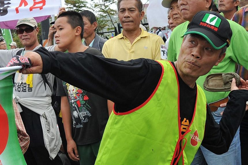 A demonstrators vented his anger by throwing a shoe at a portrait of President Ma Ying-jeou (centre) , who is also the Kuomintang chairman, outside the national congress of the ruling Kuomintang (KMT) party in Taichung, on Nov 10, 2013. -- PHOTO: AFP