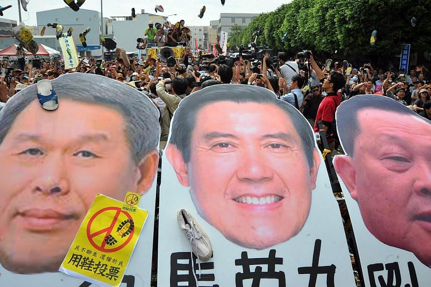 Demonstrators vent their anger by throwing shoes at a portrait of President Ma Ying-jeou (centre) , who is also the Kuomintang chairman, outside the national congress of the ruling Kuomintang (KMT) party in Taichung on Nov 10, 2013. Hundreds of angry