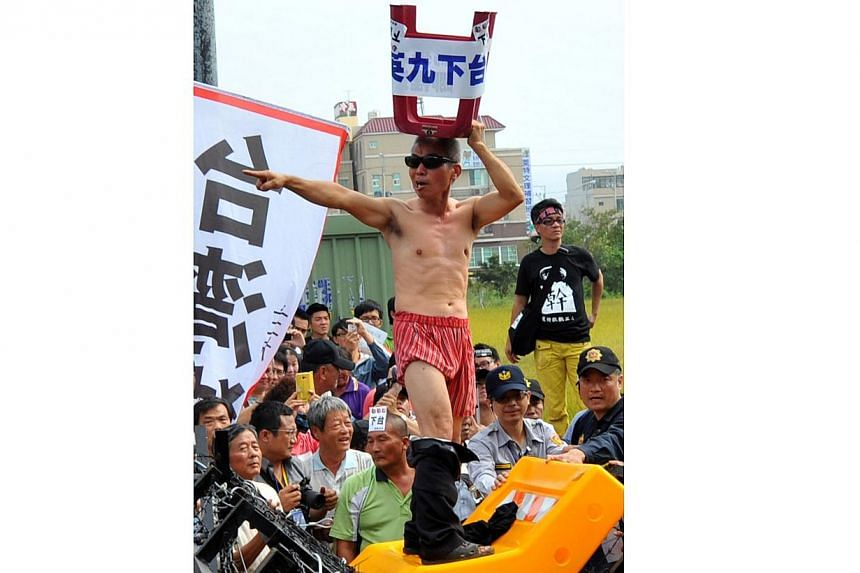 A demonstrator chants slogans and displays a sloganposter at the protest outside the national congress of the ruling Kuomintang (KMT) party in Taichung, on Nov 10, 2013. -- PHOTO: AFP