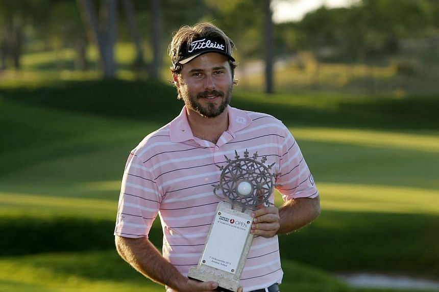 Victor Dubuisson of France poses with his trophy after his victory at the inaugural Turkish Airlines Open in the south west city of Antalya, Nov 10, 2013. France's Victor Dubuisson upstaged some of golf's biggest stars including World No. 1 Tiger Woo