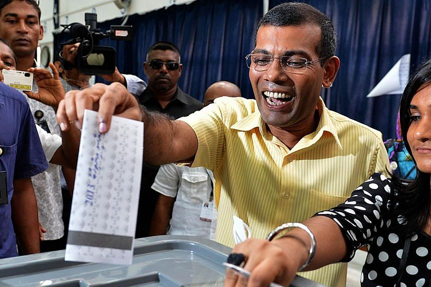 Maldivian former president and presidential candidate Mohamed Nasheed (second right) casts his vote at a local polling station in Male on Nov 9, 2013. The Supreme Court in the Maldives ordered the suspension of run-off presidential elections due to t