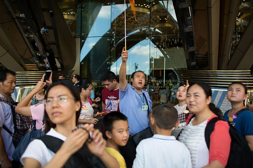 Tourists stand outside of the main entrance of the Casino Grand Lisboa, operated by SJM Holdings in Macau, China. SJM Holdings said on Monday its third-quarter net profit rose 10.3 per cent to HK$1.83 billion (S$294 million) versus HK$1.66 billi