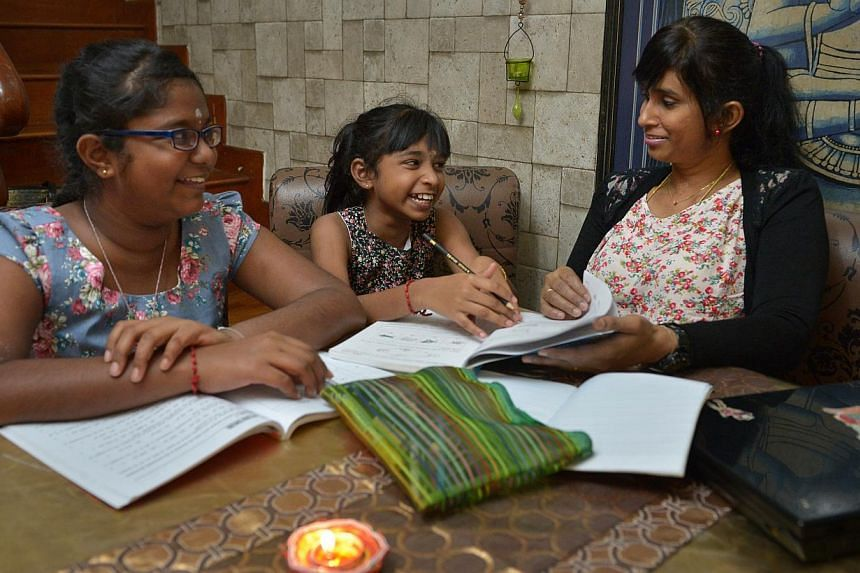 Madam P. Amuthavalli Pillai, 40, helping her daughters S. Reshaleni, 12, and S. Rosihenie, 10, with homework. The girls are in Sinda's Project Teach, a school-based tuition programme. -- ST PHOTO: KUA CHEE SIONG