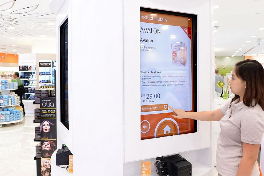A staff member demonstrating the use of a touchscreen monitor at the newly opened Guardian Plus store in Takashimaya. Such touchscreens and tablets help patrons locate products and find out about promotions.
