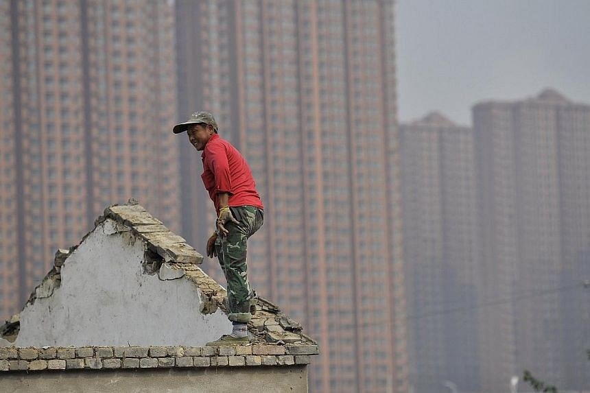 A man stands on the top of a building as farmers' houses are demolished to make space for new property to be built, in front of a residential compound in Hefei, Anhui province, on Oct 19, 2013. Land reform and household registration are two key issue