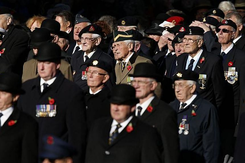 Military veterans look on as Queen Elizabeth II stands to honour the dead during ceremonies marking Remembrance Sunday at the Cenotaph in central London on Nov 10, 2013. Queen Elizabeth II led Britain in paying tribute to its war dead as the country