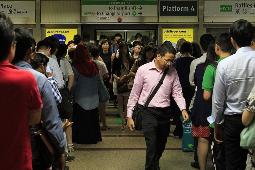 Commuters at Raffles Place MRT Station during peak hour on Oct 7, 2013. The Government has accepted all the recommendations made by the Fare Review Mechanism Committee last week, Transport Minister Lui Tuck Yew told Parliament on Monday. -- ST