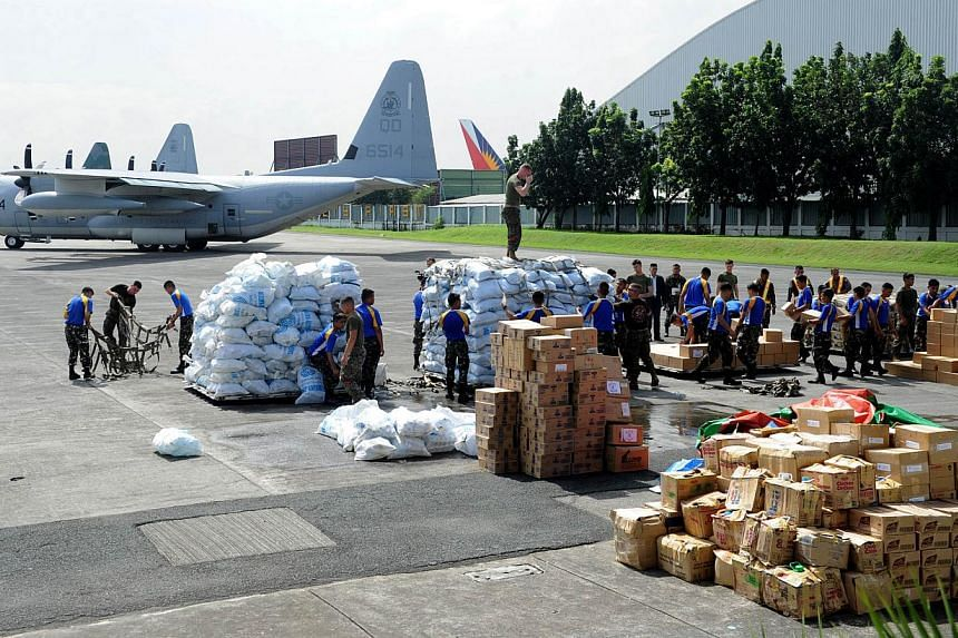 Philippine and US military personnel load relief goods for Tacloban on board a US C-130 plane for victims of Super Typhoon Haiyan that hit the Cental Philippines, at a military base in Manila on Nov 11, 2013. Australia boosted its funding for relief