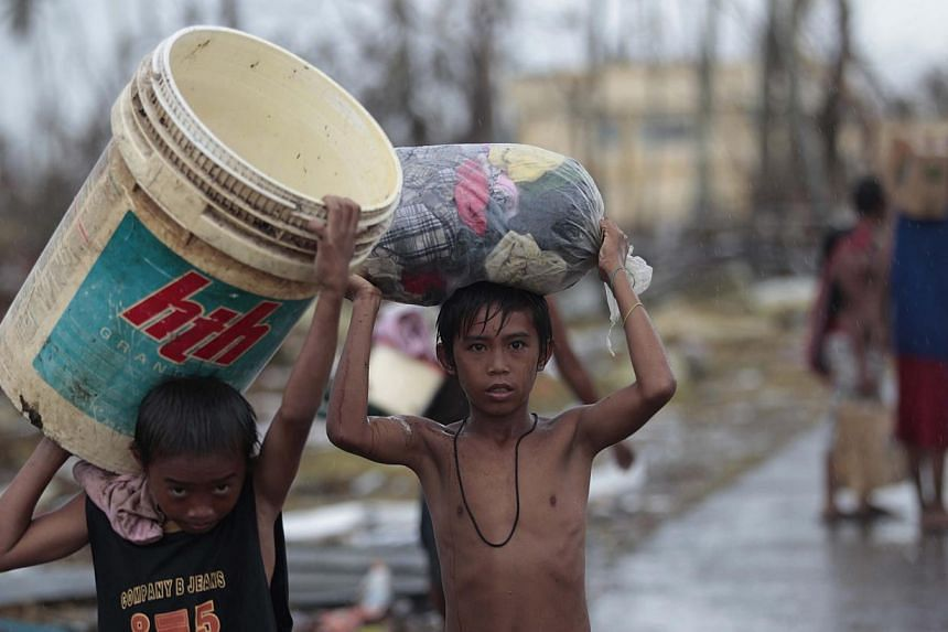 Survivors carry clothes along a road at typhoon-ravaged Tacloban city, Leyte province, central Philippines, on Tuesday, Nov 12, 2013. After seeing the horror brought by Typhoon Haiyan's wrath to central Philippines late last week, the world can't hel