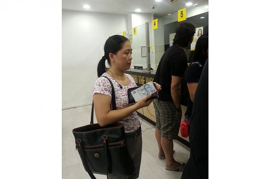 Filipina Elvie Madahan (above) has only $50 in savings but that is not stopping the maid in Singapore sending the money back to family members affected by Typhoon Haiyan. -- ST PHOTO: AMELIA TAN
