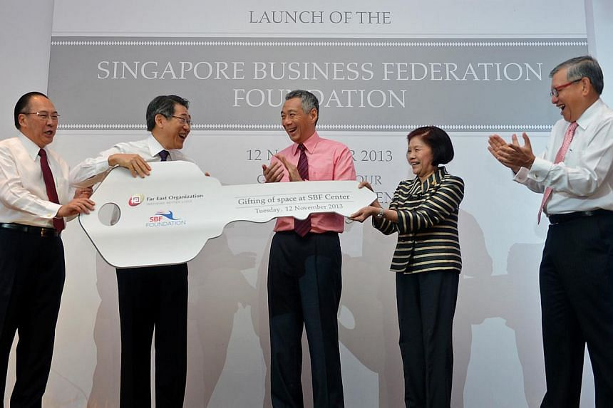 Prime Minister Lee Hsien Loong (centre), Mr Tony Chew (left), Council Chairman of Singapore Business Federation (SBF), and Mr Ho Meng Kit (right), CEO of SBF, witnessing the presentation of a huge key from Mr Philip Ng (second from left), CEO of Far