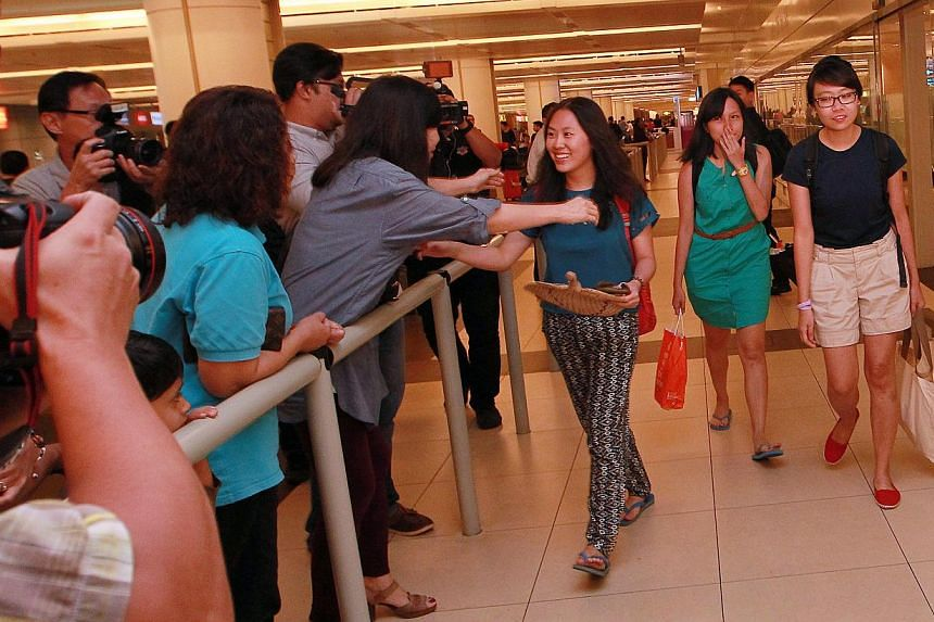 (From right) Ms Eileen Heng, Ms Alyssa Chee and Ms Vanessa Chong arrive at Changi Airport on Tuesday, Nov 12, 2013. The three young women were greeted with flowers, balloons, and tearful hugs from friends and family who, just a day ago, wer