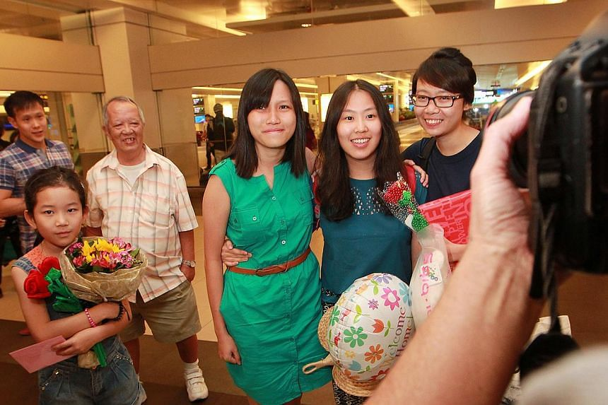 (From right) Ms Eileen Heng, Ms Vanessa Chong, and Ms Alyssa Chee pose for a group photograph for the media after they arrive at Changi Airport on Tuesday, Nov 12, 2013. -- ST PHOTO: NEO XIAOBIN