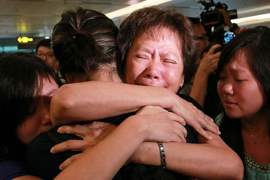The family and loved ones of Ms Eileen Heng, 23, give her a hug upon her return to Singapore on Tuesday, Nov 12, 2013. -- ST PHOTO: NEO XIAOBIN