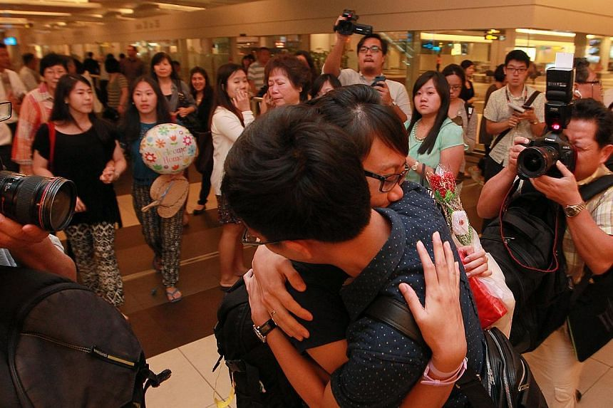 Ms Eileen Heng, 23, gets a hug from her friends as she arrives at Changi Airport on Tuesday, Nov 12, 2013.-- ST PHOTO: NEO XIAOBIN