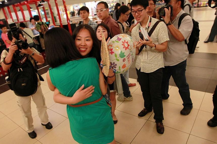 Ms Vanessa Chong hugs Ms Alyssa Chee (in green) as they bid each other farewell after they arrive at Changi Airport on Tuesday, Nov 12, 2013.-- ST PHOTO: NEO XIAOBIN