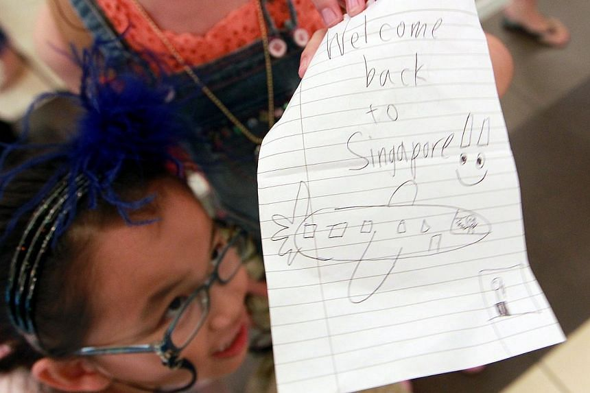 Nine-year-old Kok Mei Fang stares at a handwritten note by her sister Kok Mei Xuan (not pictured), 10, to welcome their relative Ms Alyssa Chee back home on Tuesday, Nov 12, 2013.-- ST PHOTO: NEO XIAOBIN