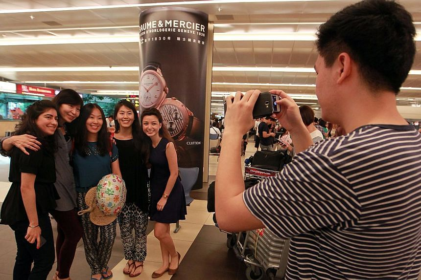 Family and friends of Ms Vanessa Chong (third from left) pose for a group photograph as she returned home to Singapore from Manila on Tuesday, Nov 12, 2013.-- ST PHOTO: NEO XIAOBIN