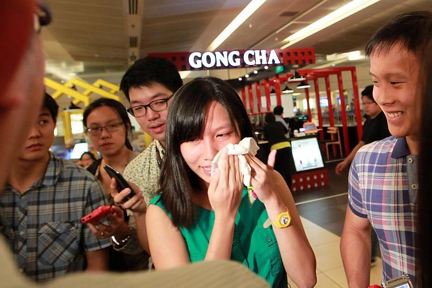 Ms Alyssa Chee wipes her tears during a media interview as her boyfriend (right) looks on by her side on Tuesday, Nov 12, 2013. -- ST PHOTO: NEO XIAOBIN