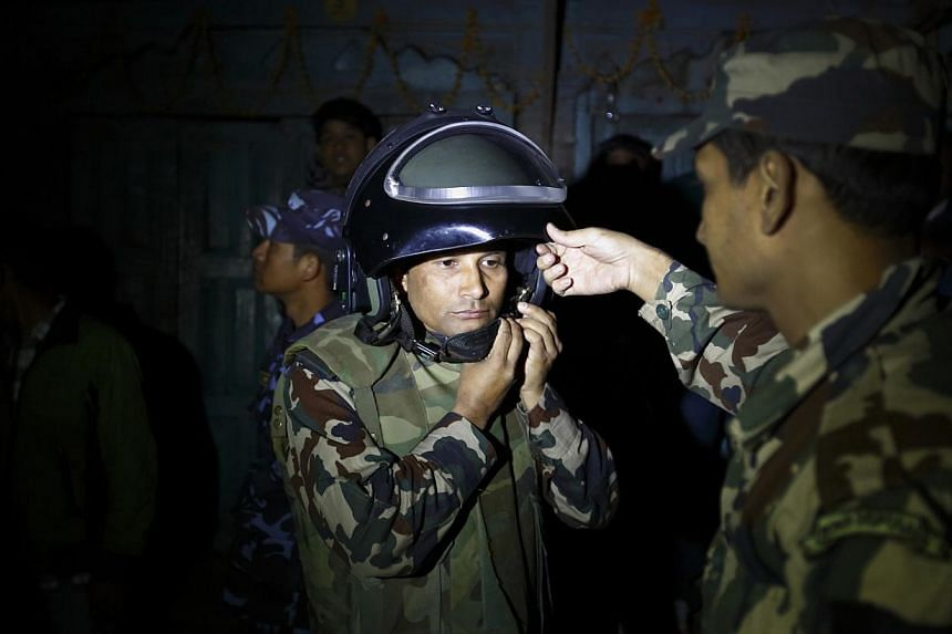 A member of a bomb disposal team preparing to approach a suspected bomb that was hanged on electricity wires in Kathmandu on November 12, 2013. Police suspected that the suspicious package was a bomb and destroyed it using a controlled detonation. It