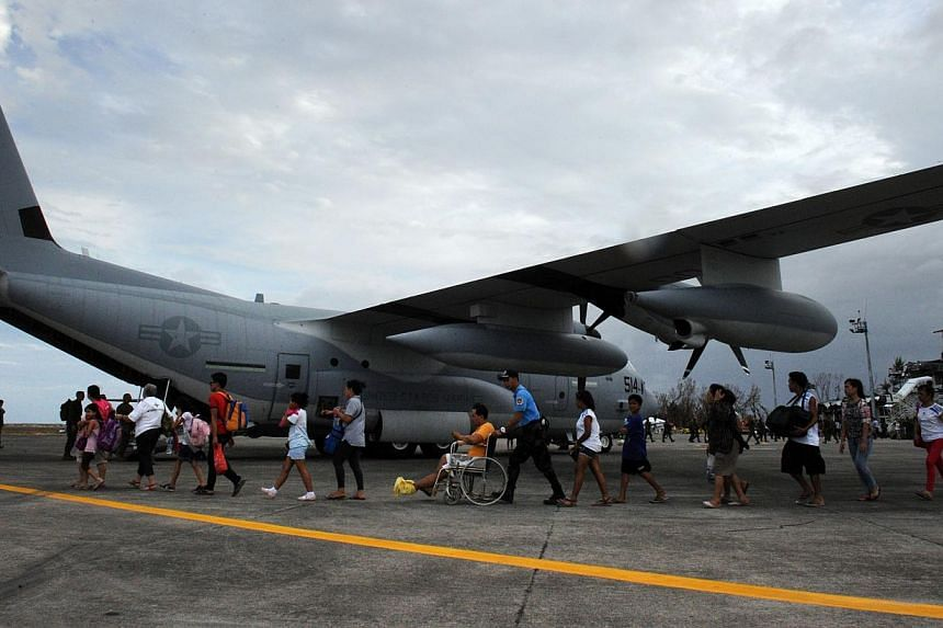 Survivors of super Typhoon Haiyan board a US military C-130 plane for Manila after the plane arrived carrying relief supplies at Tacloban airport in the central Philippines on Nov 11, 2013. Filipinos across the United States rallied to support aid ef