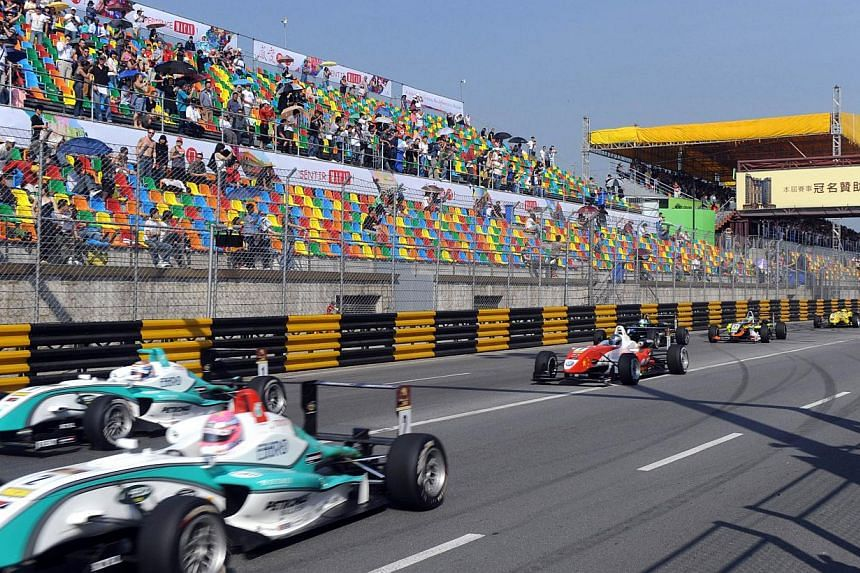Formula Three cars racing past spectators during a qualifying race of the 55th Macau Grand Prix in Macau on Nov 15, 2008. As it celebrates its 60th edition, the Macau Grand Prix - one constant in a time of rapid change for the Chinese territory - is