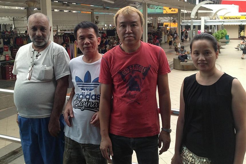 Hougang Central shopkeepers (from left) Malkit Singh, 55, Choi A Chao, 56, Stanley Lai, 46, and Liu Qijie, 38. Behind them is an ongoing trade fair at the communal space in front of Hougang Mall. Mr Singh, Mr Choi and Mr Lai were among the five who w