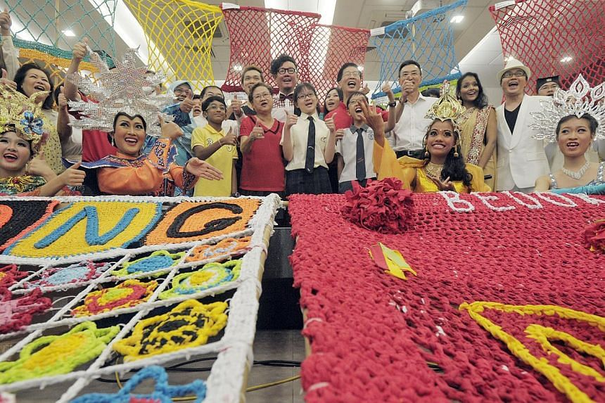 Chingay 2014 participants show part of the two hand-knitted tapestries, each 360m long, which will be featured in the parade on Wednesday, Nov 13, 2013. Singapore's largest batik paintingwill have 130 panels featuring flower motifs including Si