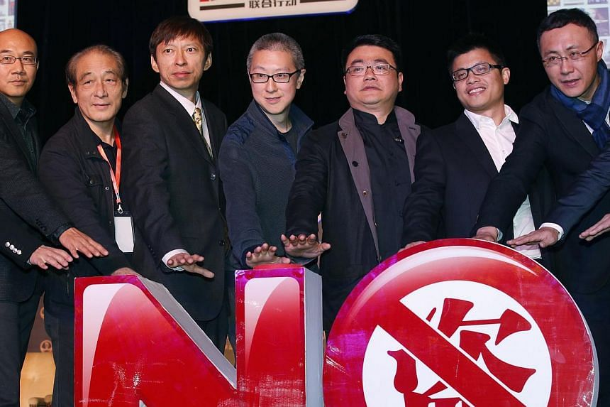 Sohu CEO Charles Zhang (third from left) and Youku-Todou CEO Victor Koo (fourth from left) pose with other attendants in front of an installation symbolising action against copyright violation during their joint news conference in Beijing on Wednesda
