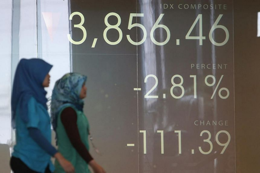 Women walk in front of a screen of the Indonesia Stock Exchange in Jakarta on Aug 28, 2013.Indonesian shares fell to their two-month lows on Wednesday, Nov 13, 2013, as investors cut risk exposure ahead of third-quarter current account data, wh