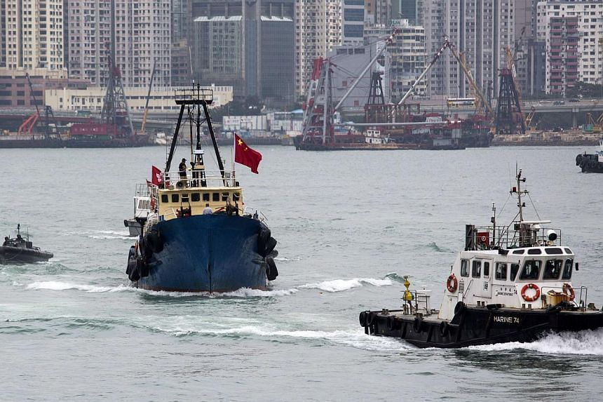 Hong Kong fishing vessel Kai Fung No 2 (second from left) attempts to depart for the disputed Senkaku or Diaoyu islands, as a police boat intercepts it, in Hong Kong on Wednesday, Nov 13, 2013.Hong Kong blocked a group of Chinese activists from