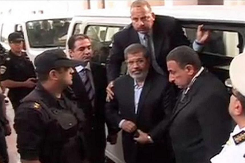 Ousted former Egyptian President Mohamed Mursi (centre) gets out of a van as he arrives on the first day of his trial, at a courthouse in Cairo, in this still image taken from video provided by Egypt's Interior Ministry on Nov 4, 2013.Mursi sai