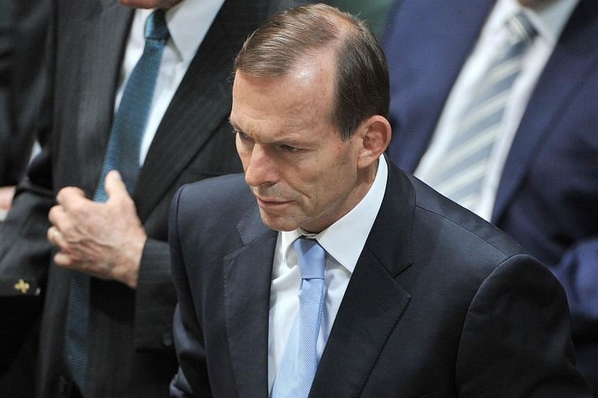 Australian Prime Minister Tony Abbott takes the oath at the opening of the 44th Parliament in Canberra on Nov 12, 2013. Australia's new conservative Prime Minister Tony Abbott on Wednesday moved to abolish a carbon tax designed to combat climate chan