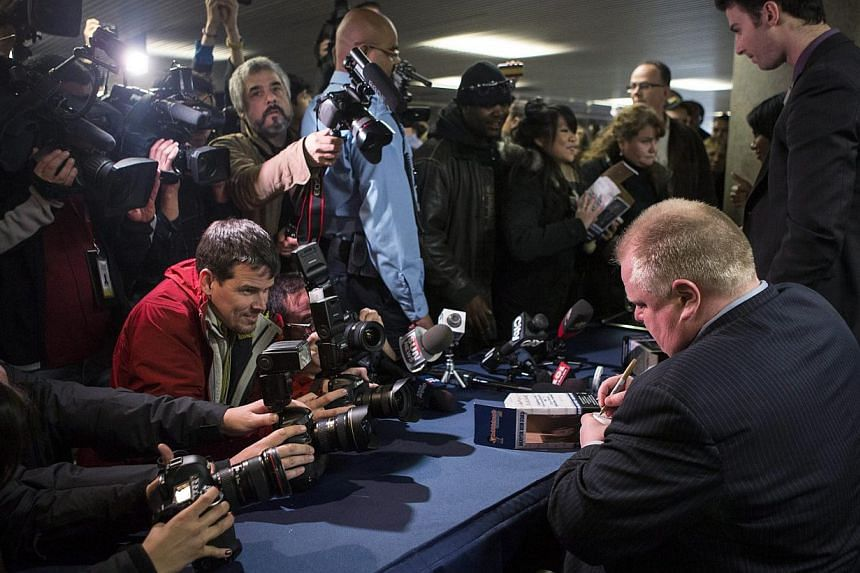 Toronto mayor Rob Ford autographs a bobblehead doll in his likeness on Nov 12, 2013, at city hall in Toronto. Hundreds of people lined up at Toronto City Hall on Tuesday to buy a limited-edition bobblehead doll of embattled Mr Ford, and by mid-aftern