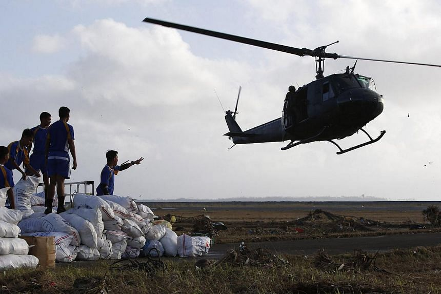 A military helicopter prepares to land to airlift relief supplies for super Typhoon Haiyan victims in Tacloban city, central Philippines, on Nov 11, 2013. The United States military has ordered two amphibious ships to the Philippines to help victims