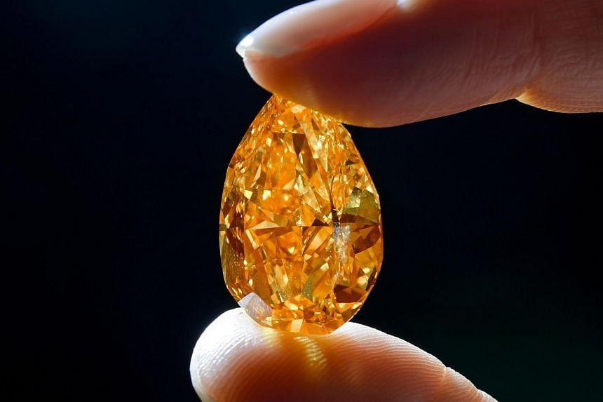 "A model shows ""the Orange"" a 14.82-carat pear-shaped, vivid orange diamond during a press preview on Oct 31, 2013 in Geneva. A spectacular and rare orange diamond, the largest known gem of its kind, was on Tuesday auctioned off for a record US$3"