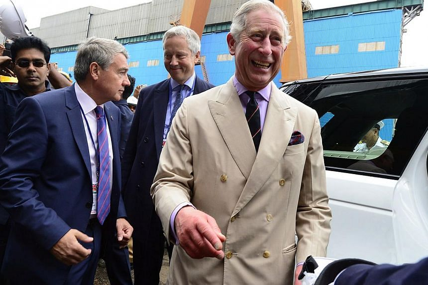 Prince Charles smiles as he interacts with officials during a visit to a shipyard to see India's first Indigenous Aircraft Carrier INS Vikrant in Kochi, India, Tuesday, Nov 12, 2013. Prince Charles is readying the paperwork to claim his pension whe