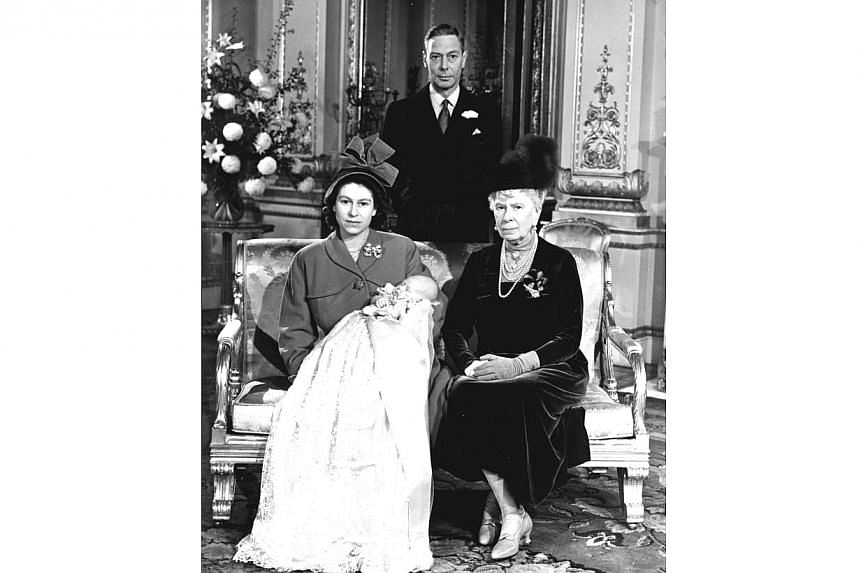 Princess Elizabeth, later Queen Elizabeth II, holds her son Prince Charles at Buckingham Palace, following his christening on Dec 15, 1948. Seated at right is her grandmother Queen Mary, the mother of her father, King George VI (background). Pr