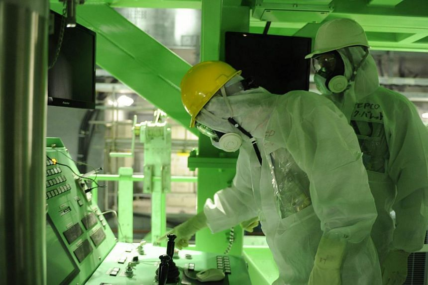 Mr Lake Barrett (right), a member of Tokyo Electric Power Co's (Tepco's) outside reform committee and independent consultant in the energy field, inspecting the No.4 reactor building at Tepco's Fukushima Daiichi nuclear power plant in Fukushima prefe