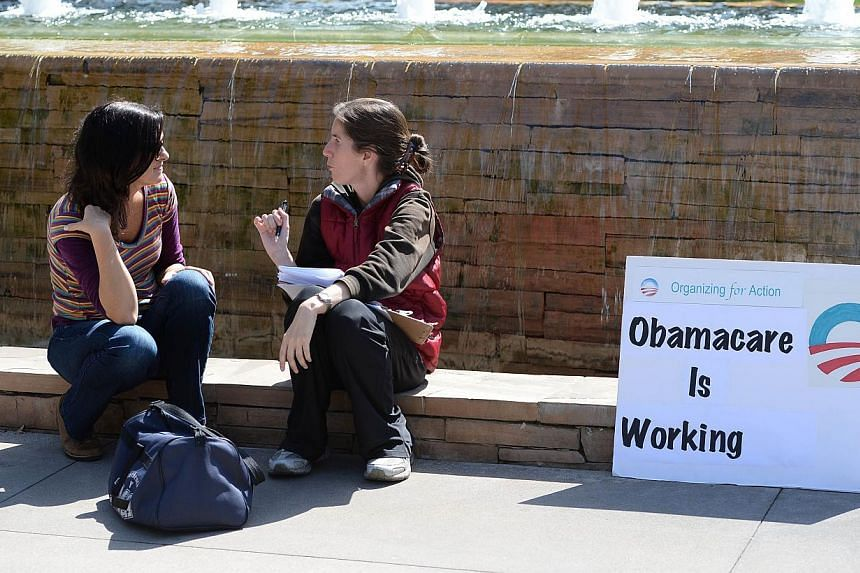 An Affordable Healthcare Act supporter (right) talks with a student (left) about the law also know as Obamacare, on the campus of Santa Monica City College in Santa Monica, California, Oct 10, 2013. Just over 100,000 people enrolled in the new U