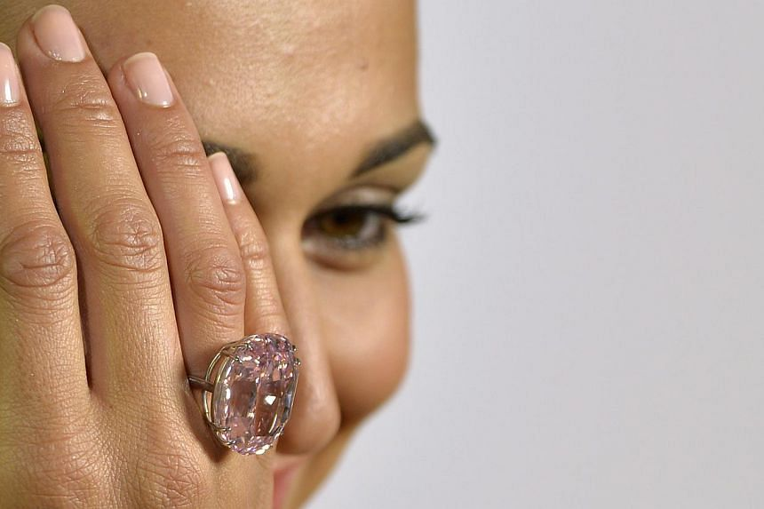 """A Wednesday, Sept 25, 2013 photo from files showing an unidentified Sotheby's employee displaying """"The Pink Star"""" diamond weighing 59.6 carat, during a preview at Sotheby's, in Geneva, Switzerland.A plum-sized diamond known as the """"Pink Star"""" w"""