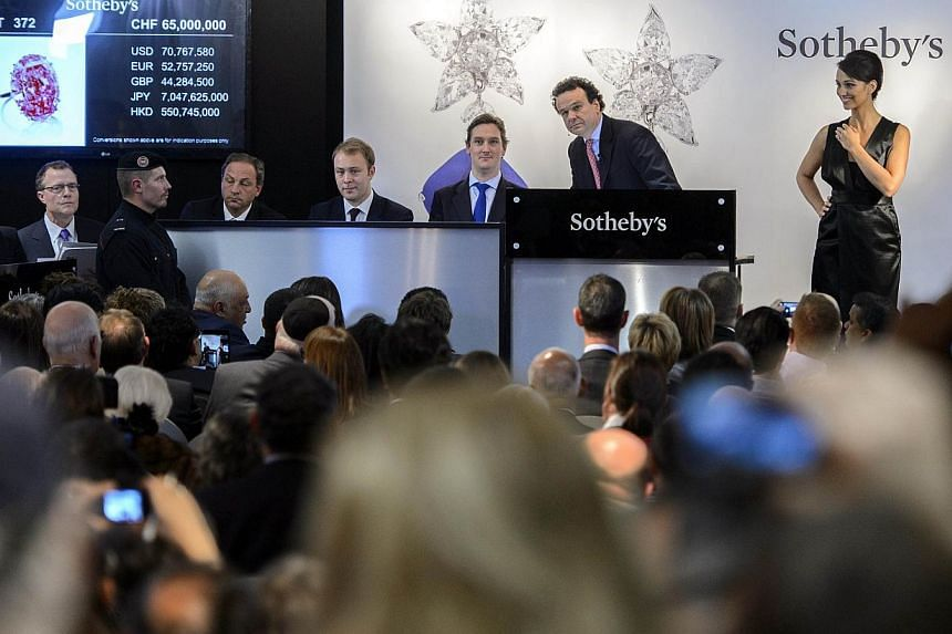 """Chairman of auctioneers Sotheby's jewellery division in Europe and the Middle East, Mr David Bennett (second right), conducts the auction of the """"Pink Star"""" diamond on Nov 13, 2012 in Geneva. The """"Pink Star"""" was auctioned in Geneva on Nov 13 for US$8"""