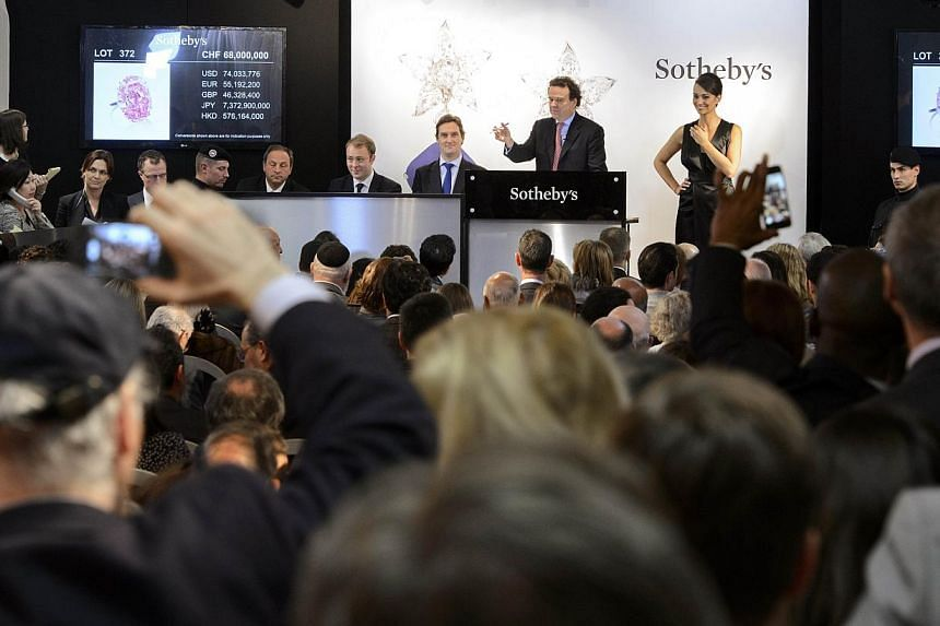 """Chairman of auctioneers Sotheby's jewellery division in Europe and the Middle East, Mr David Bennett (centre), conducts the auction of the """"Pink Star"""" diamond on Nov 13, 2012 in Geneva. The """"Pink Star"""" was auctioned in Geneva on Nov 13 for US$83 mill"""