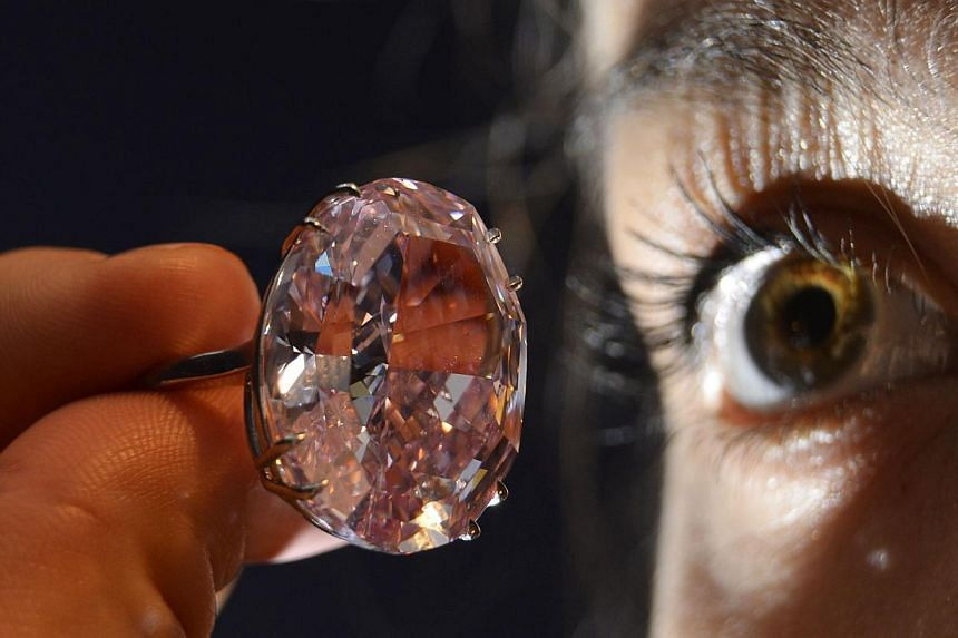 """Model Annabeth Murphy-Thomas poses with The Pink Star diamond at Sotheby's auction house in central London in this Oct 24, 2013 file photo. The """"Pink Star"""" was auctioned in Geneva on Nov 13 for US$83 million (S$104 million), a world record for a gems"""