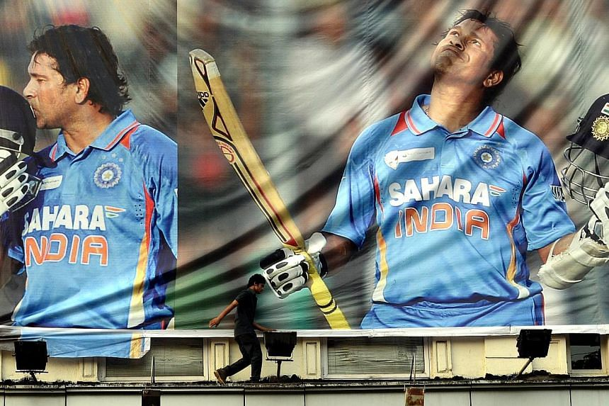 An Indian youth walks past a huge poster saluting cricketer Sachin Tendulkar on the facade of a shop in Mumbai on November 13, 2013. Sachin Tendulkar is set for an emotional farewell when he plays his 200th and final Test at home in Mumbai from Novem